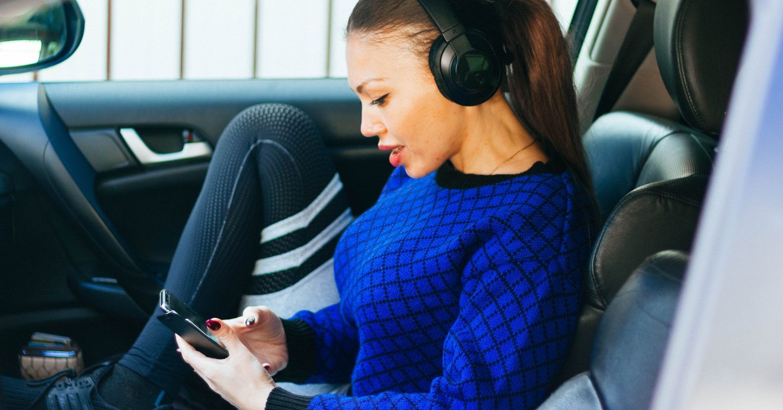 woman sitting in car listening to podcast