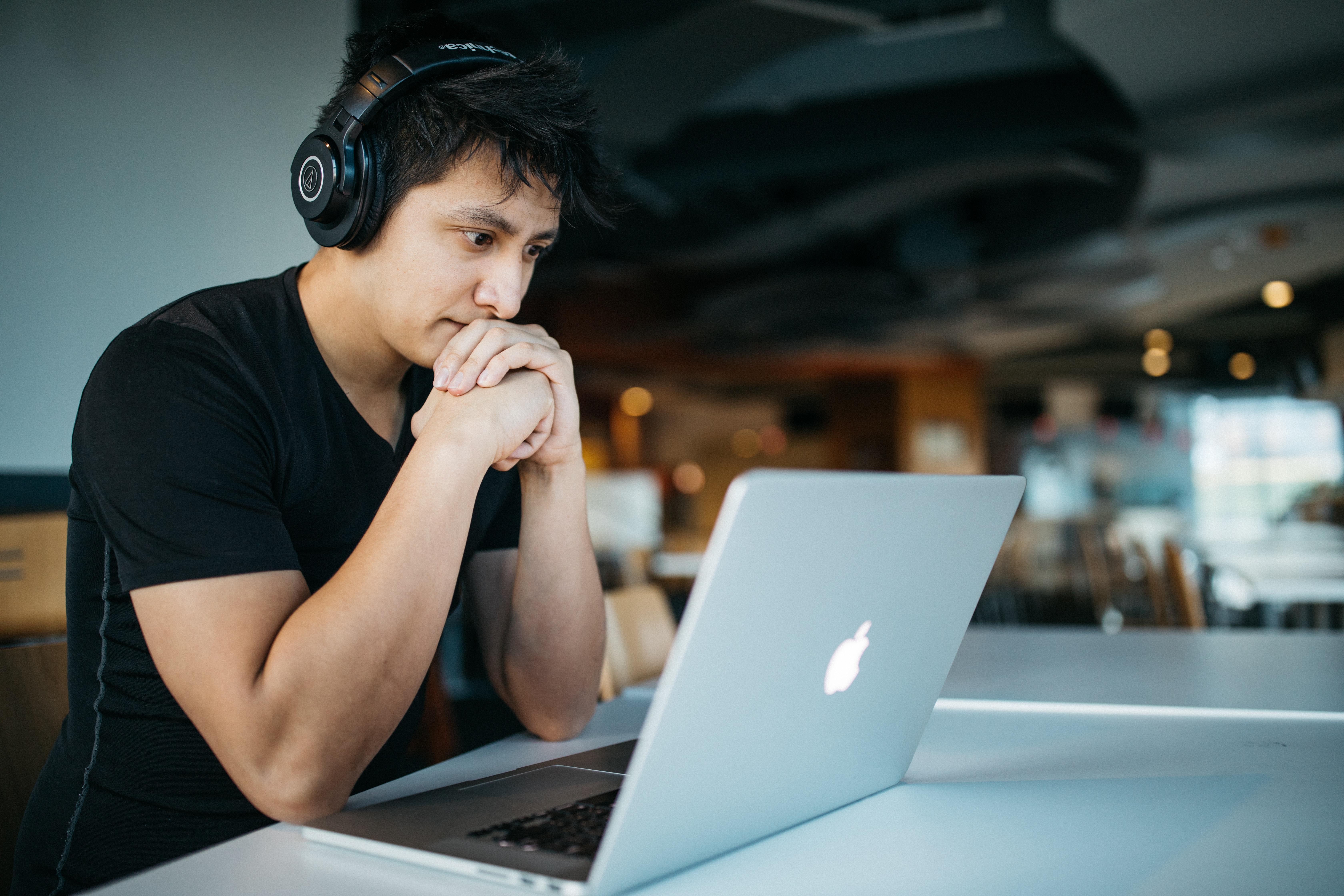 man at desk looking at laptop